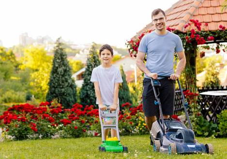 Father and son mowing backyard together. Standing and smiling.